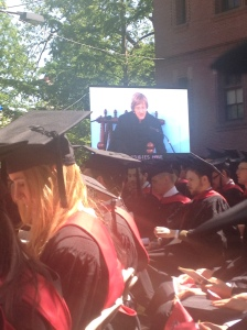 The Harvard president on big screen... saying the magic graduation words...
